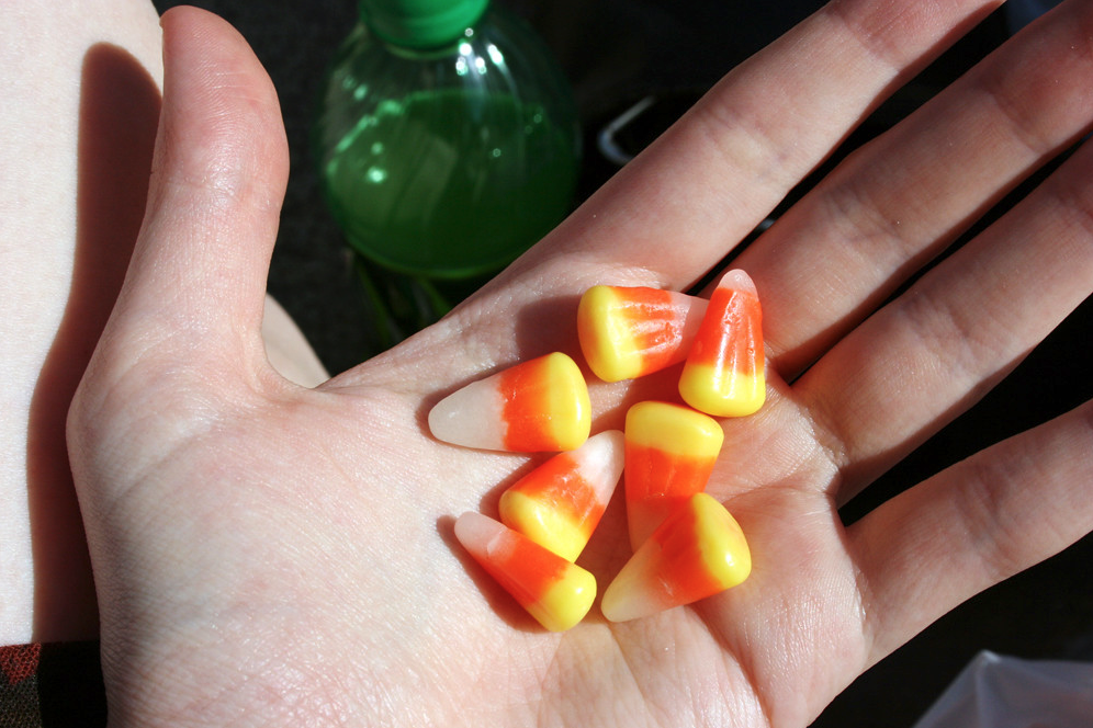 A hand holding a couple of pieces of candy corn