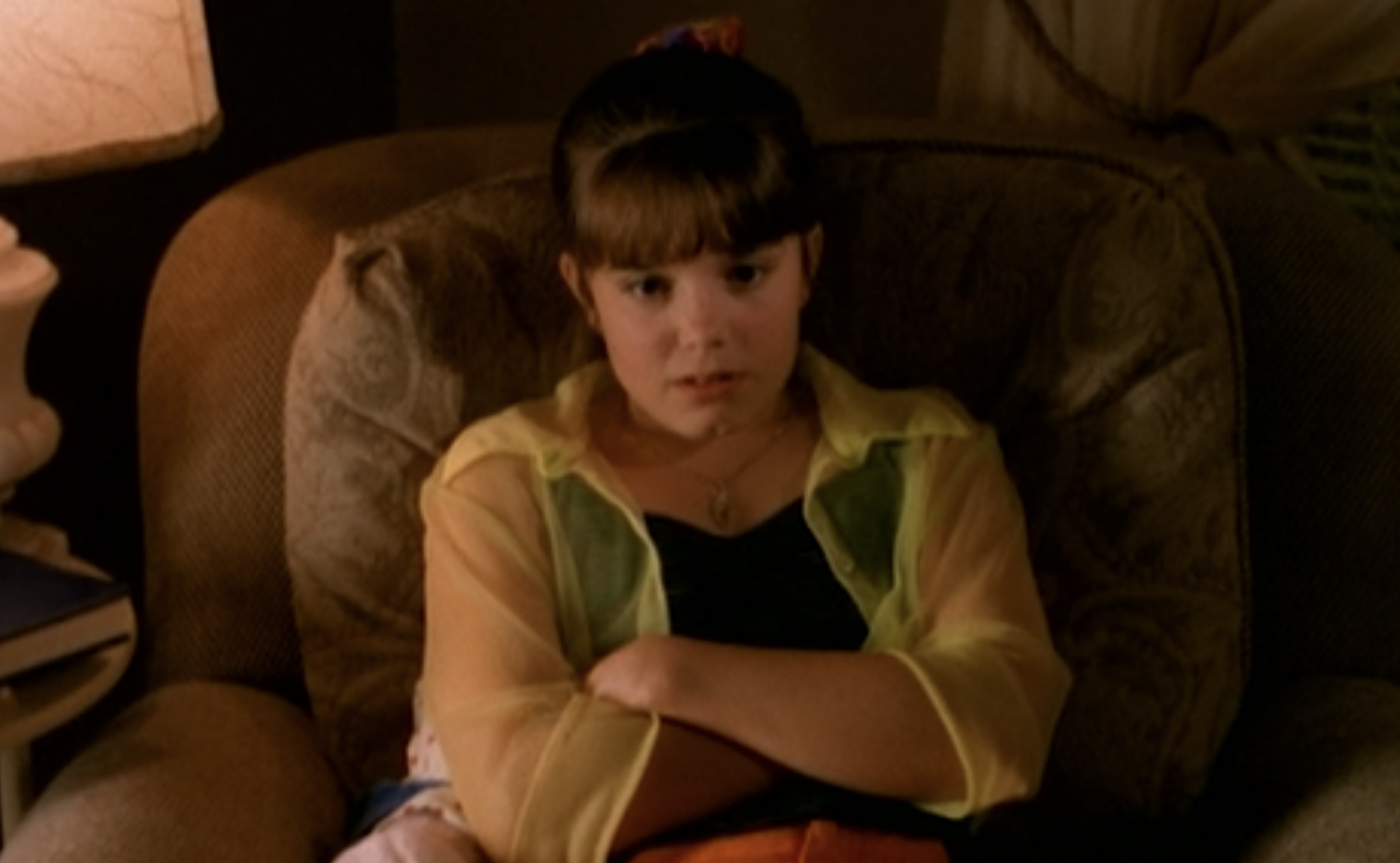 Marnie wearing a bright, see-through button-up over a dark tank top with a scrunchie holding up her hair
