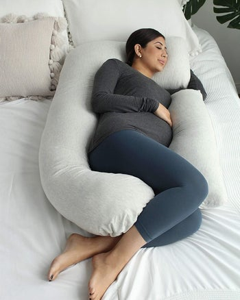 Pregnant model sleeping with the body pillow surrounding them, except for the space where it doesn't connect where they put their arm