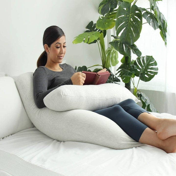 Pregnant model reading while propped on the pillow with part of the pillow under her book