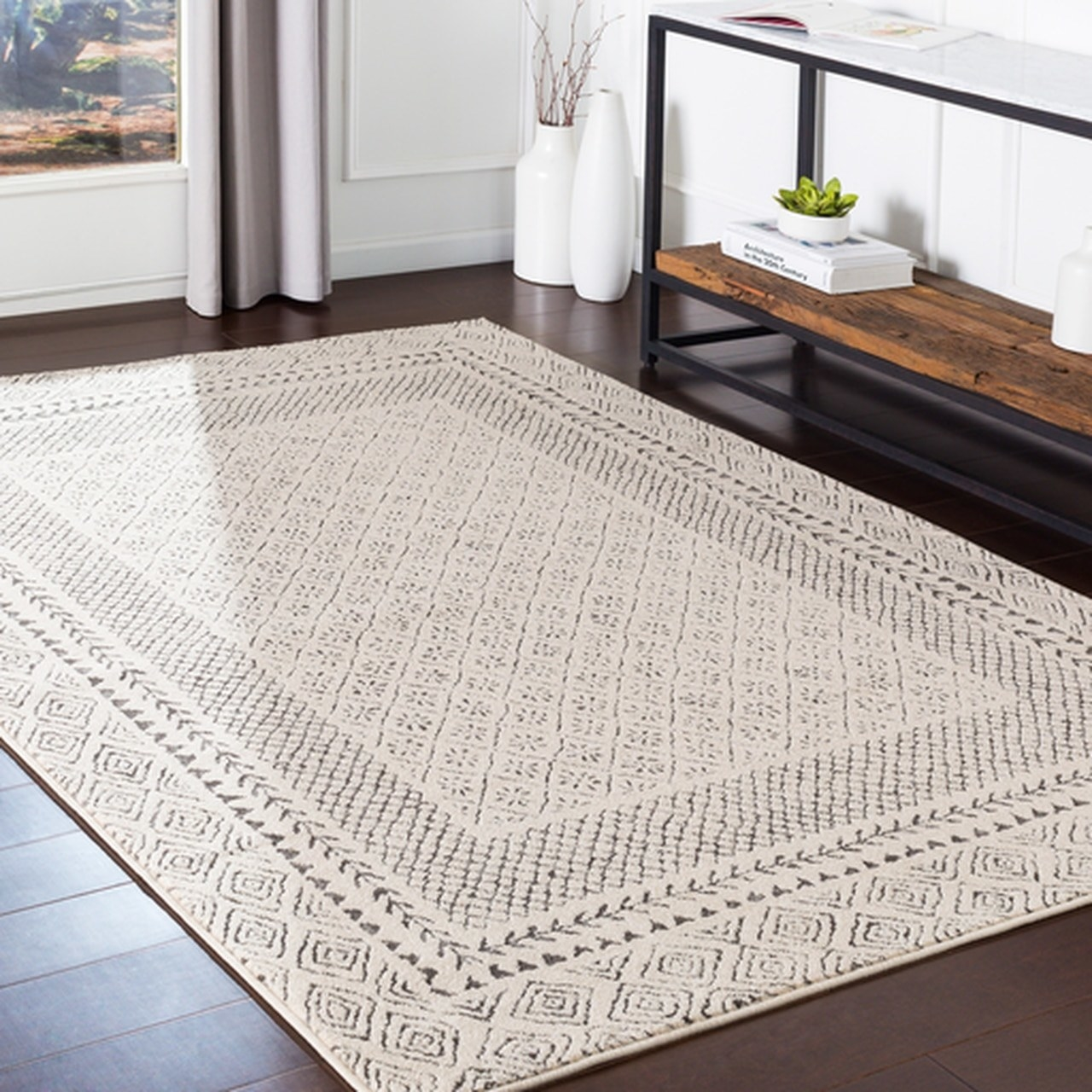 The beige and gray rug on a wooden floor