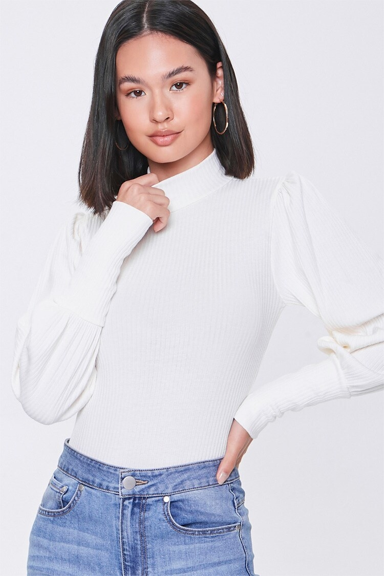 Model wearing the bodysuit, which has a mock neck and puffy sleeves, in white