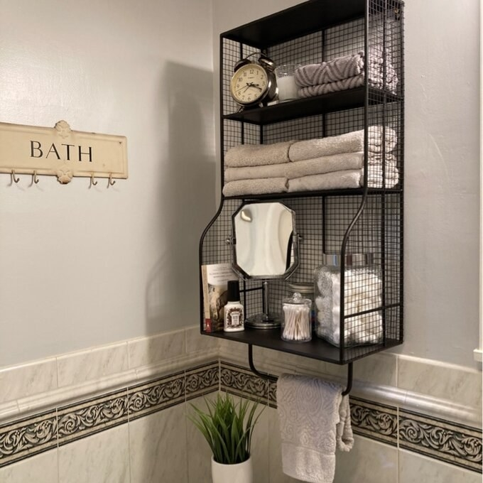 Reviewer image of the storage organizer installed in the bathroom with tons of bathroom essentials