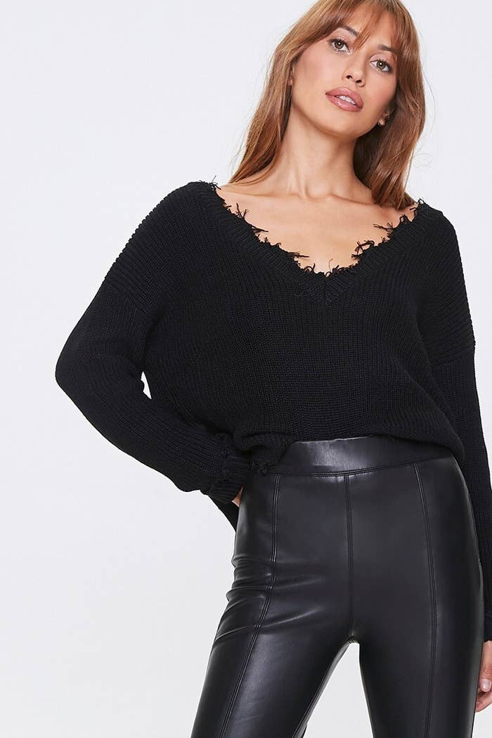 Model wearing the black sweater with high-waisted faux leather leggings