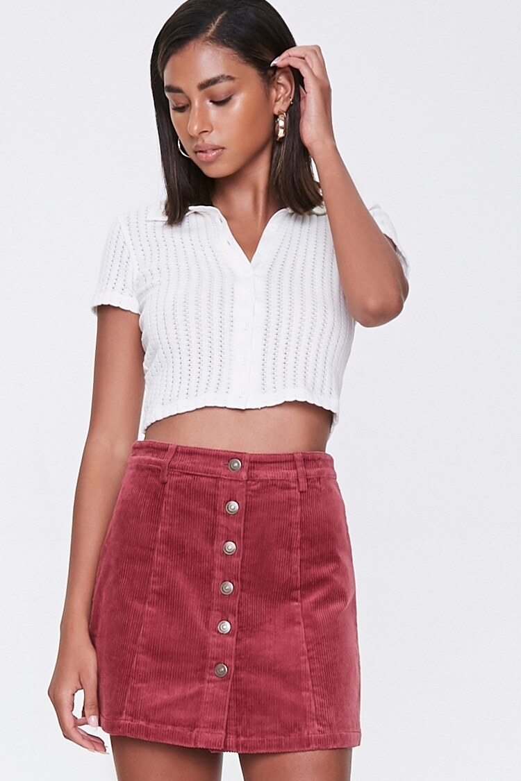 Model wearing the button-front skirt in burgundy with a cropped white polo