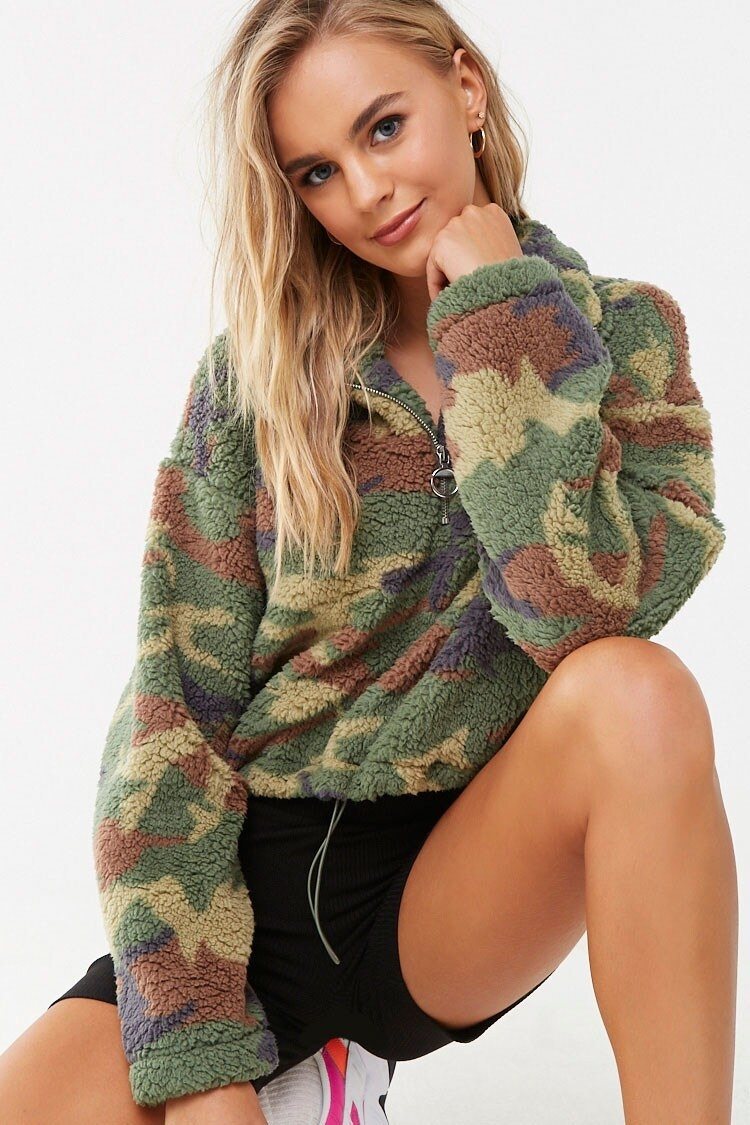Model wearing the quarter zip sherpa pullover with black shorts