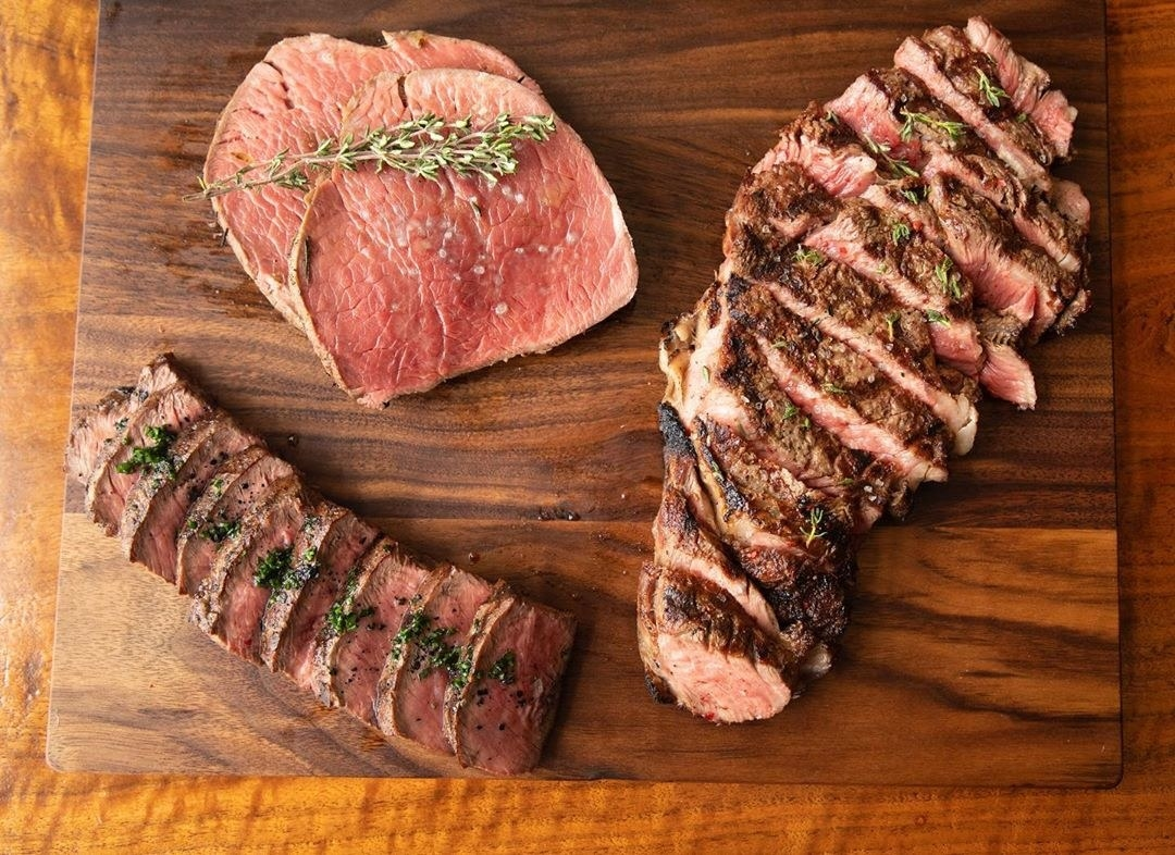 Various pieces of perfectly cooked steak on a cutting board
