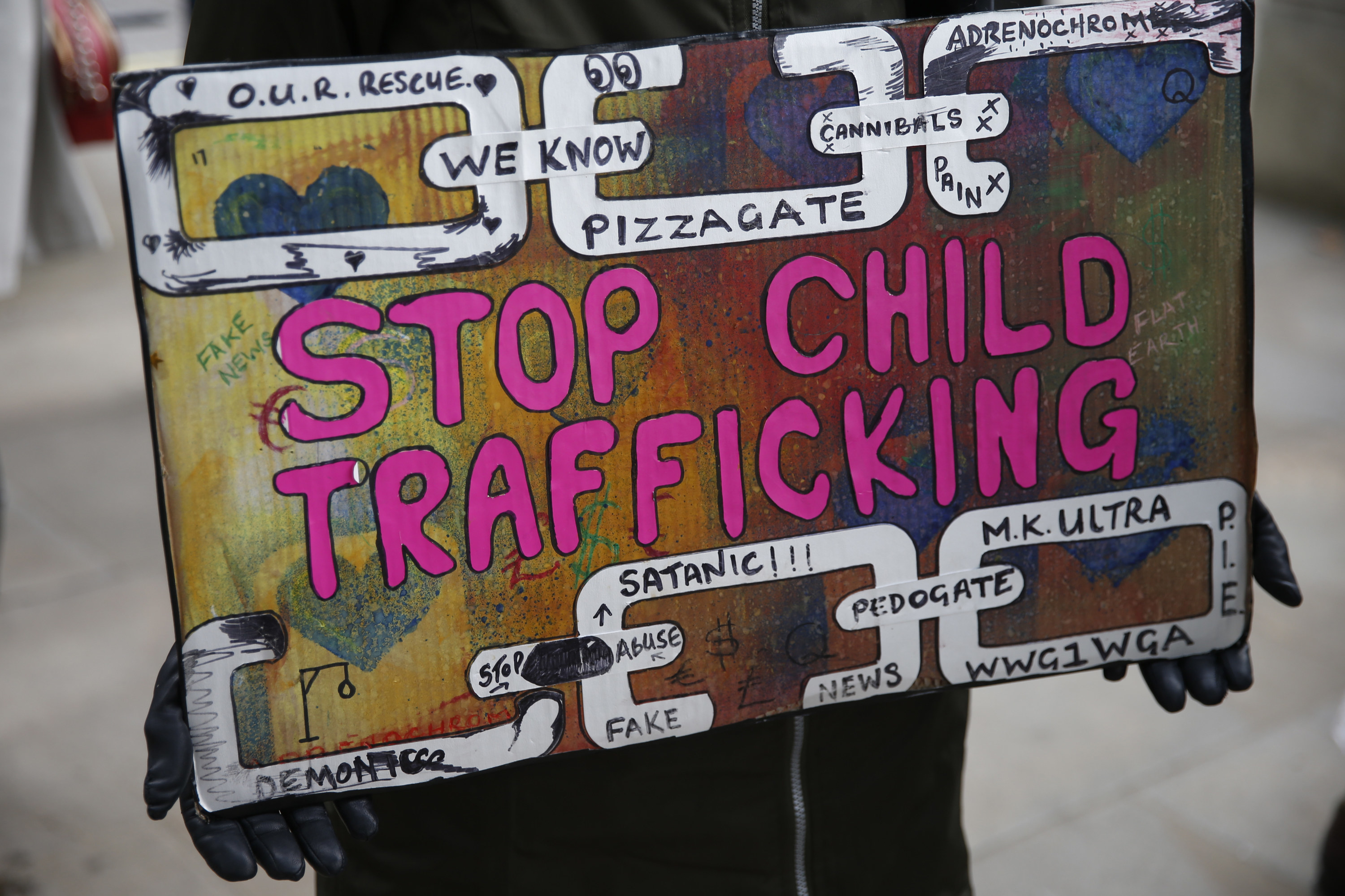 "A protester holds a sign that says ""Stop Child Trafficking"" as well as other QAnon-related slogans"