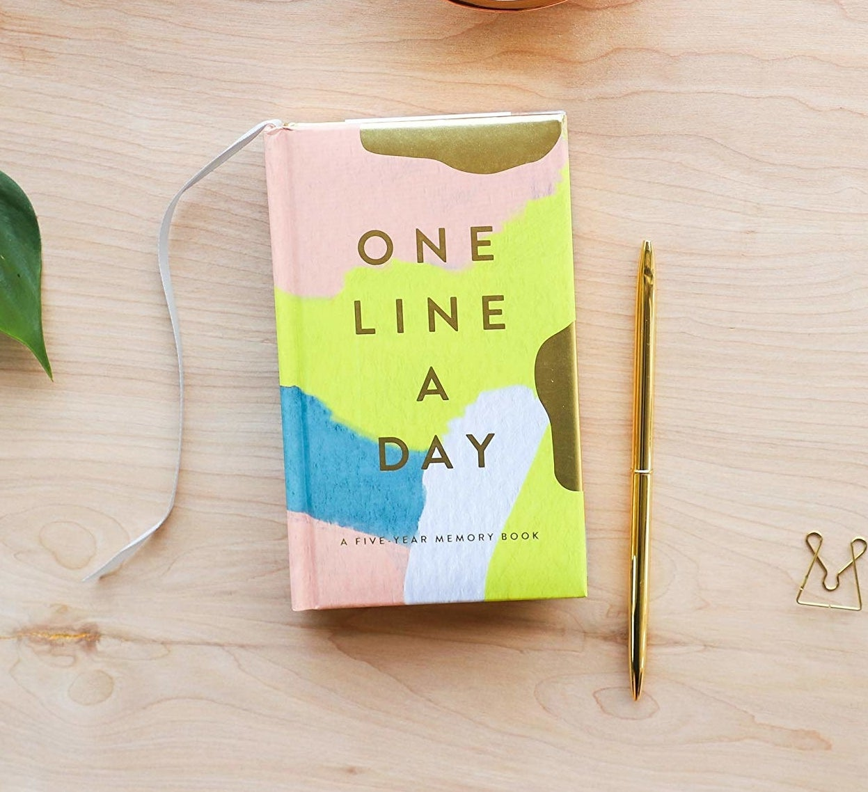 the pink, white, blue, and yellow one line a day journal