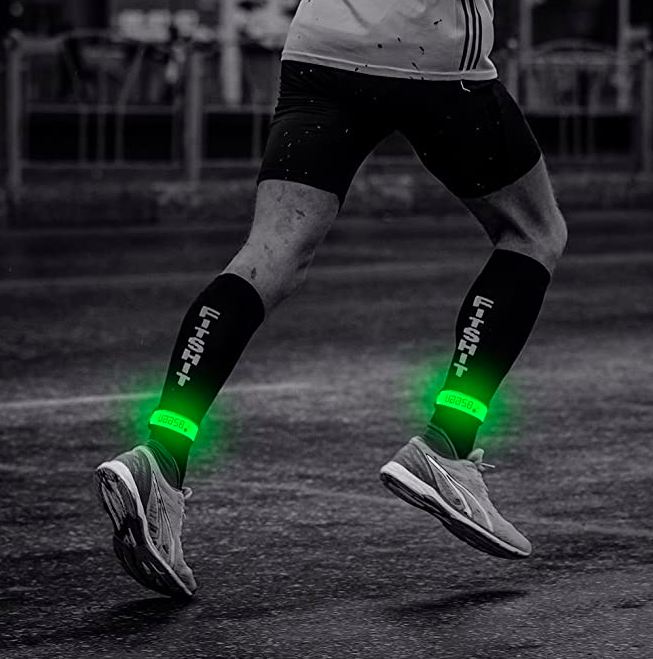 Model wears green glow-in-the-dark bands on their ankles while they run at night