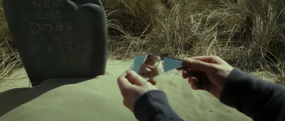 """Harry looking at the two-way mirror in """"Deathly Hallows: Part 2"""" near Dobby's grave"""
