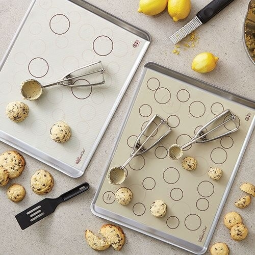 two baking sheets with white baking mats with circles as guides for cookies