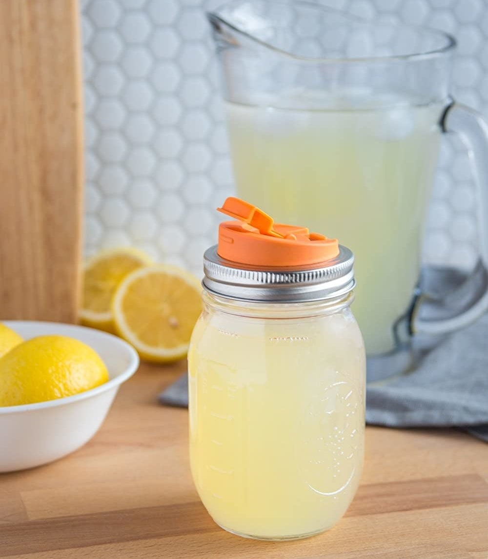 A Mason filled with lemonade that has a spout attached to the lid