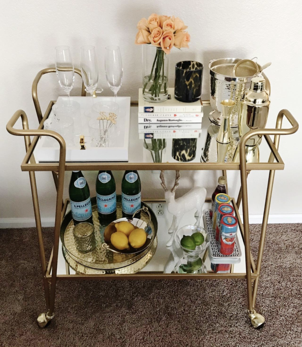 Customer showcases gold bar cart with liquors, glasses, floral arrangement and books