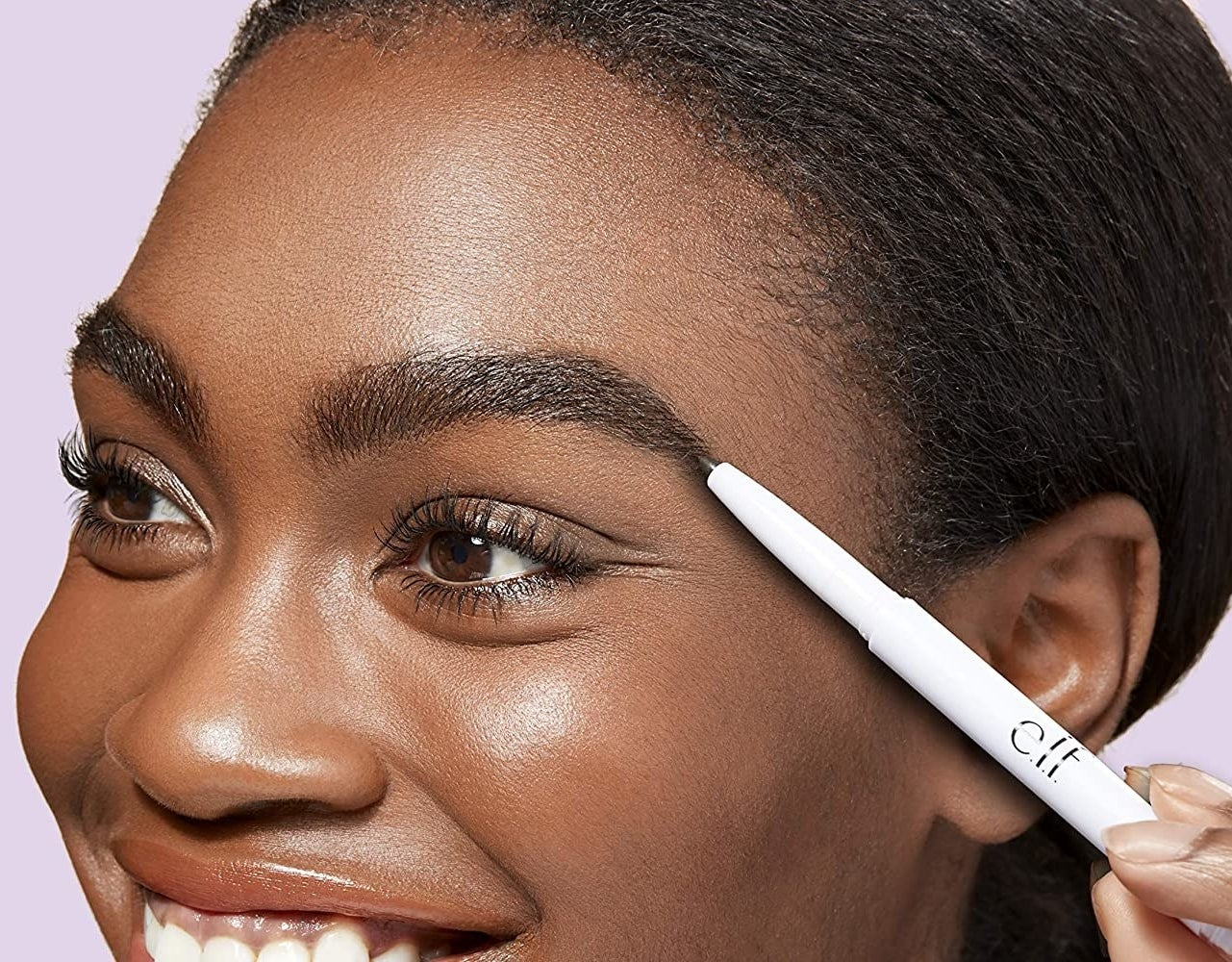 A person using a brow pencils to fill in their brows