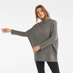 the same model now wearing the sweater as a turtleneck