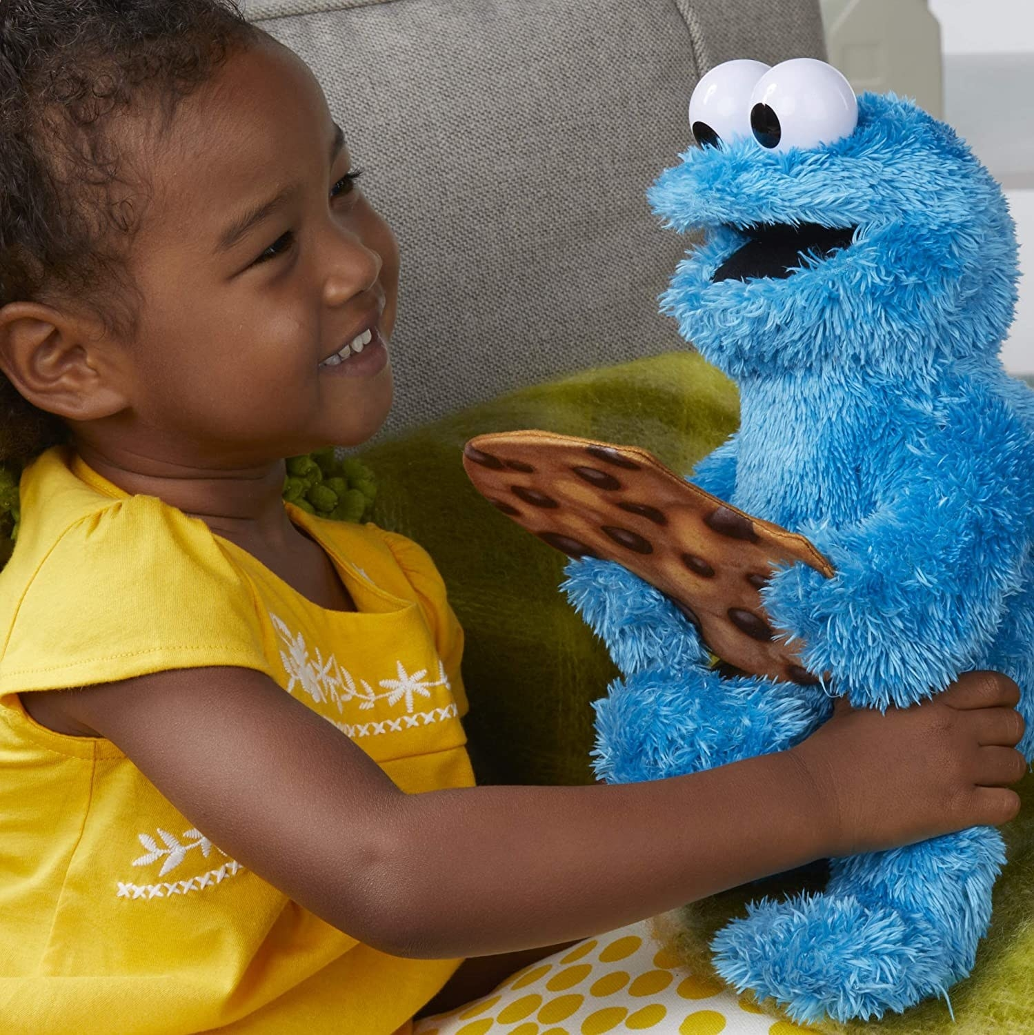 Child holding Peekaboo Cookie Monster doll