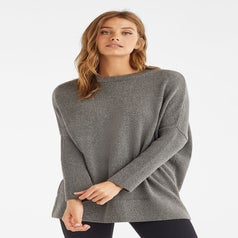 Model wearing the long sweater as a crewneck in grey
