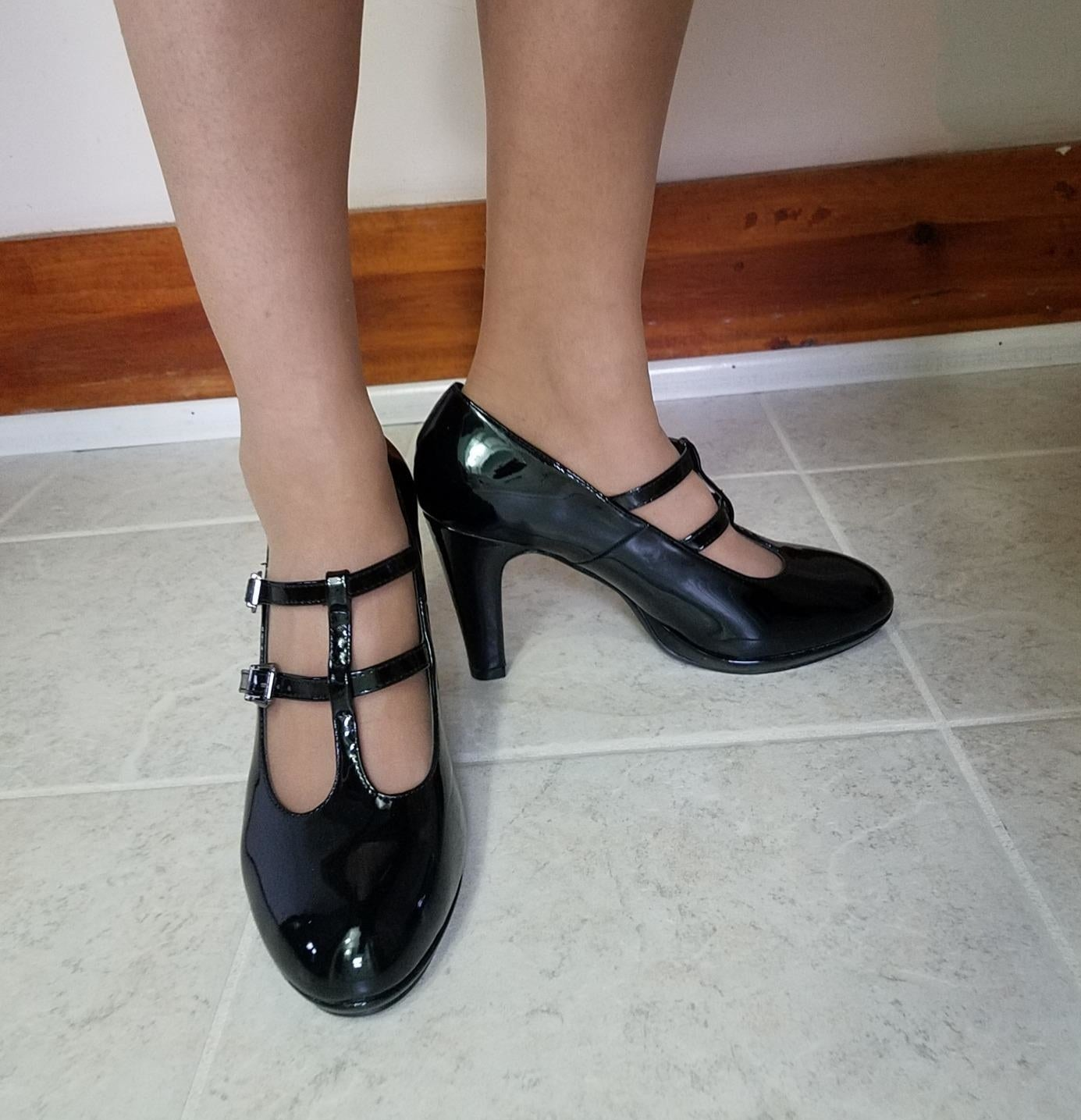 A reviewer wearing the faux patent leather high heels in black