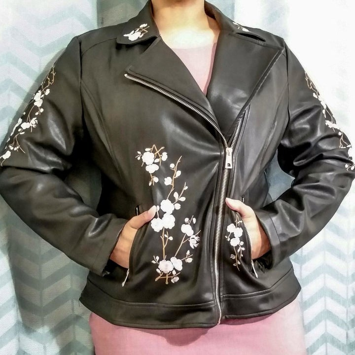 Reviewer wearing a black leather jacket with floral embroidery zipped up with both hands in the side zip pockets