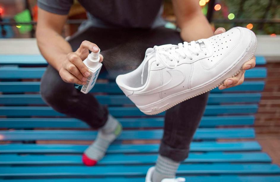 Model sprays shoe deodorizer into white Nike basketball shoe