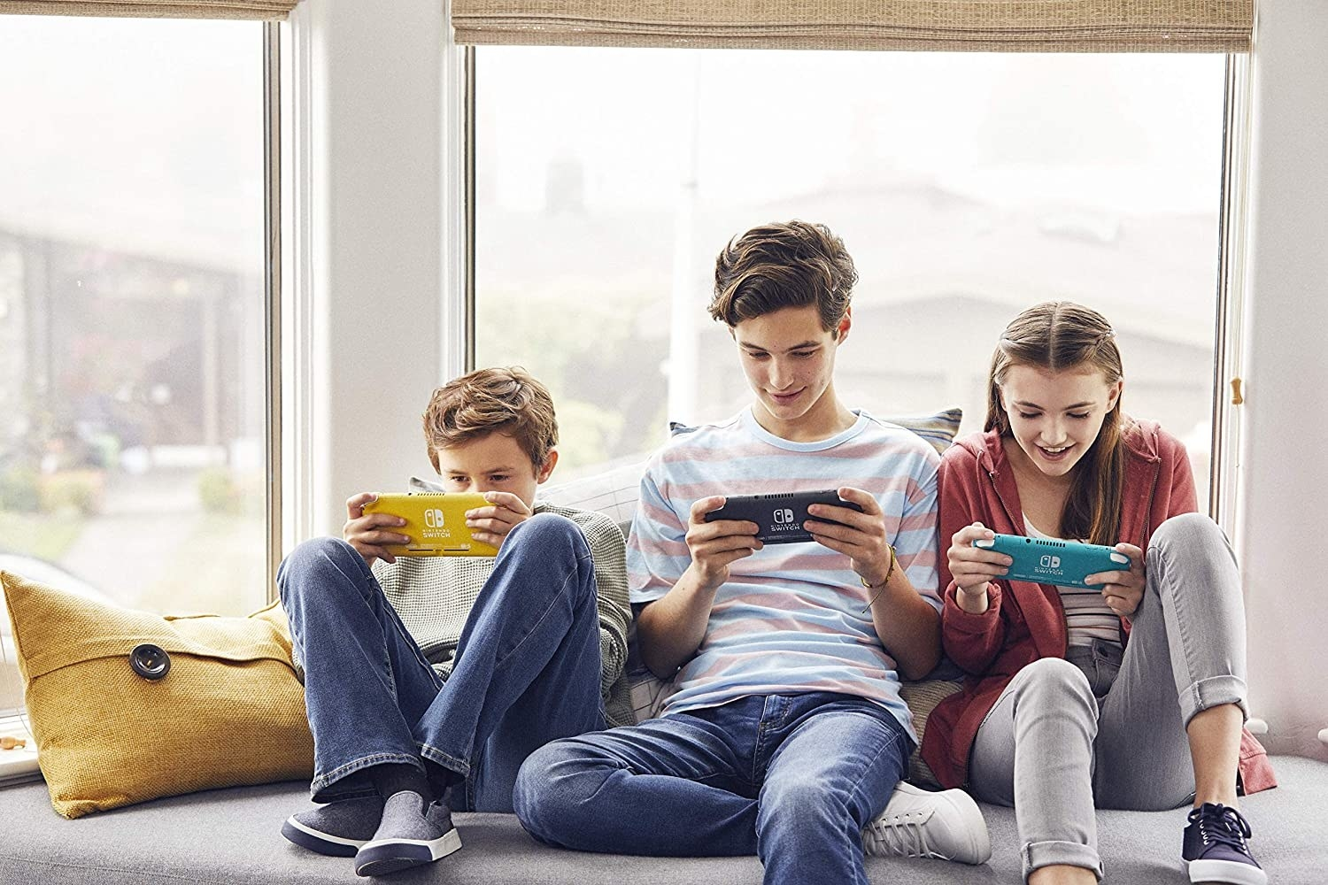 Three kids playing with the Nintendo Switch Lite