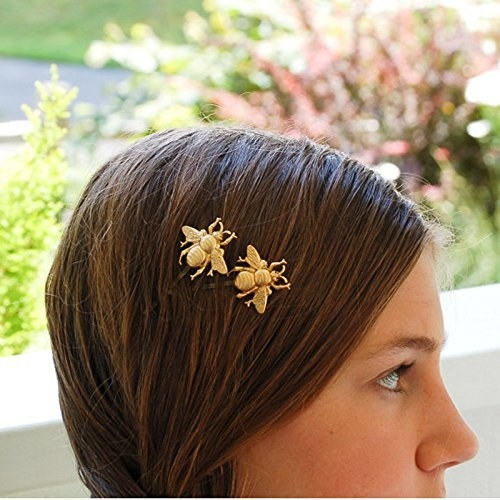 A model wearing the gold bee hairpins