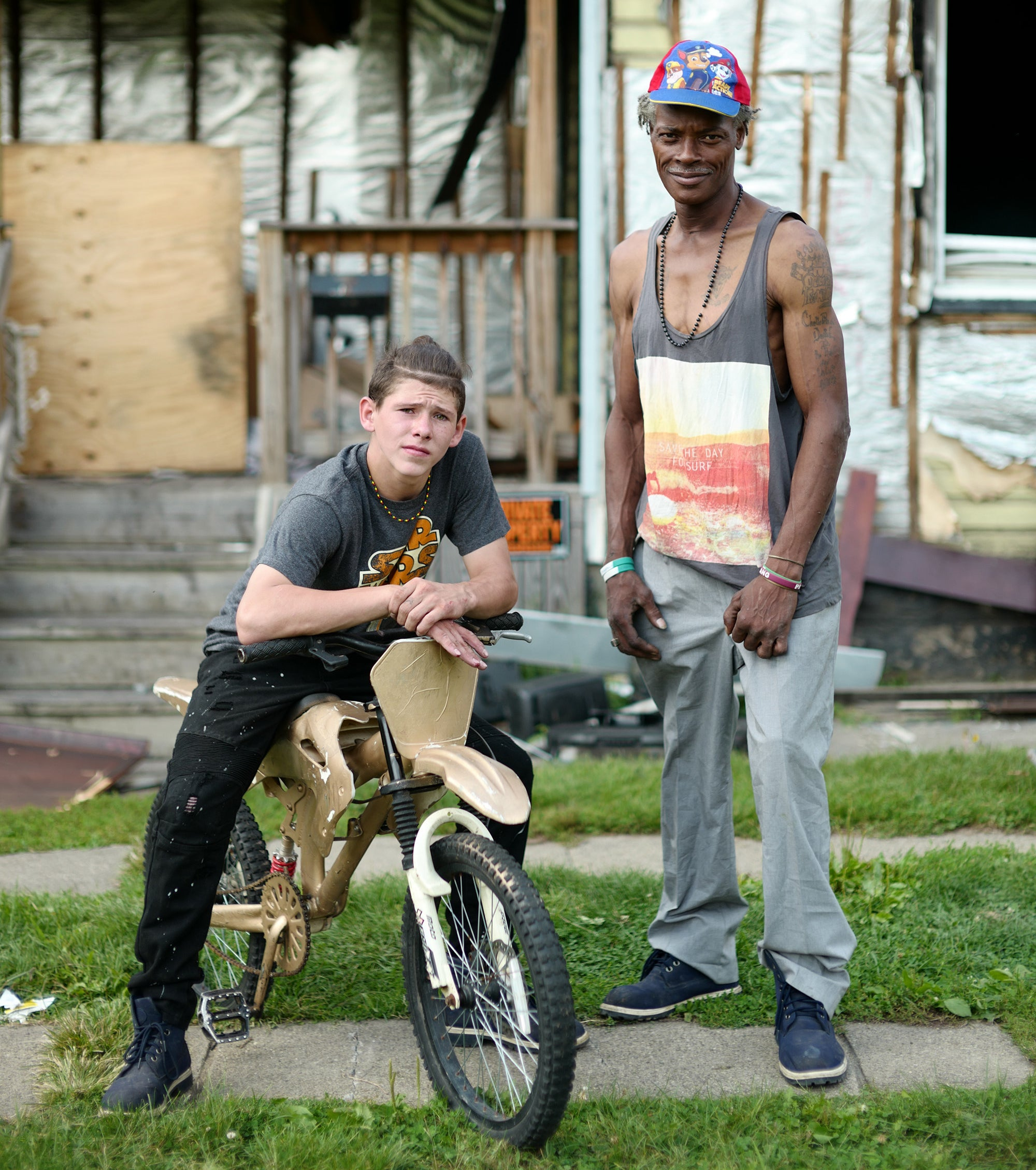 A boy on a bike and a man standing in front of a boarded-up house
