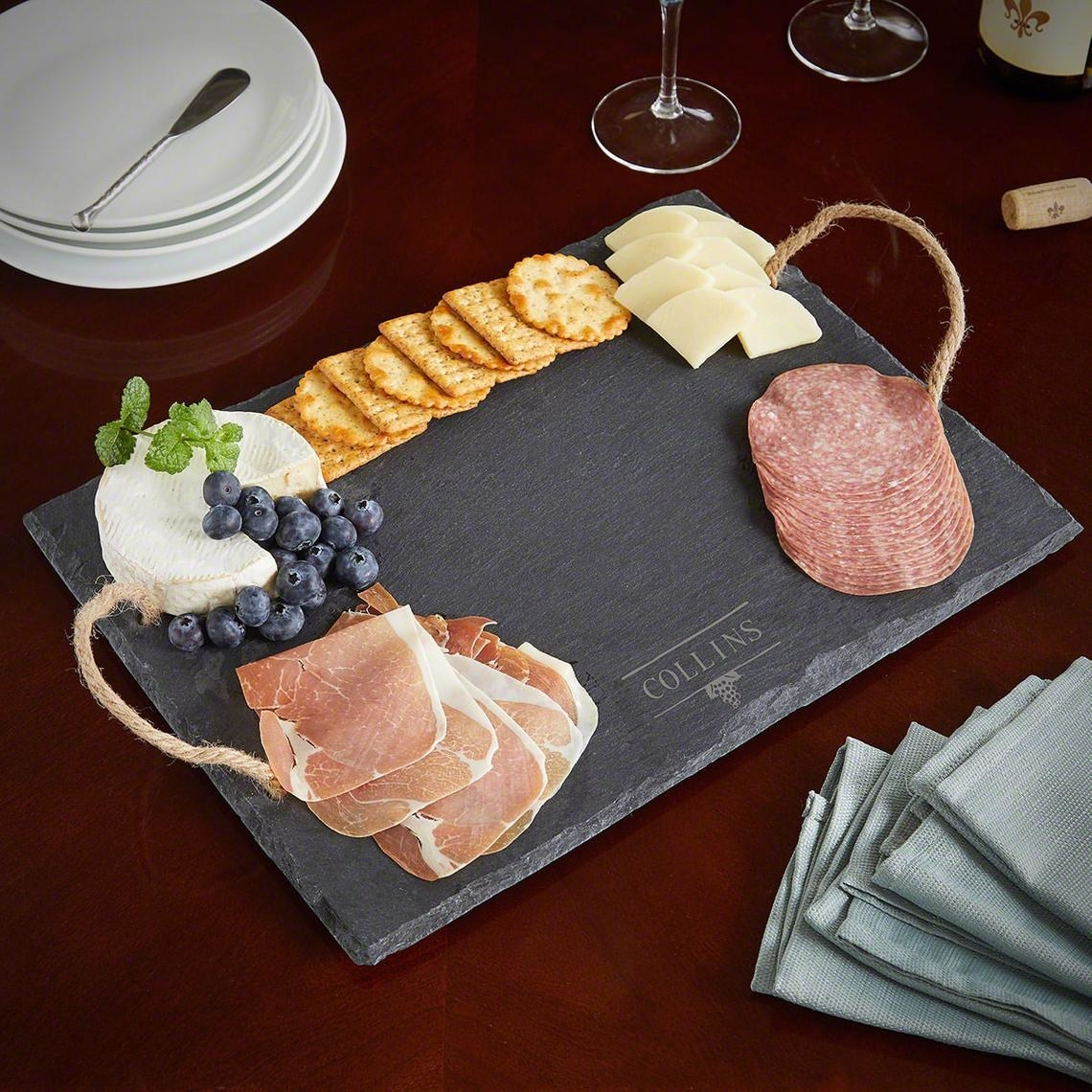A charcuterie board with meat cheese crackers and fruit