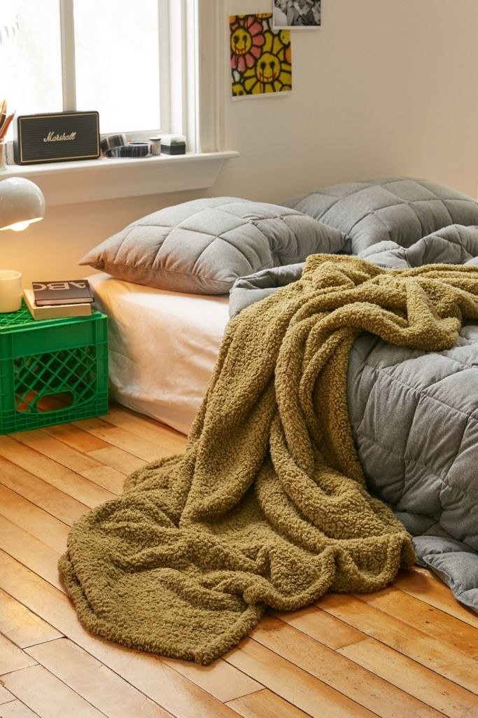 the blanket in moss green tossed over the bed