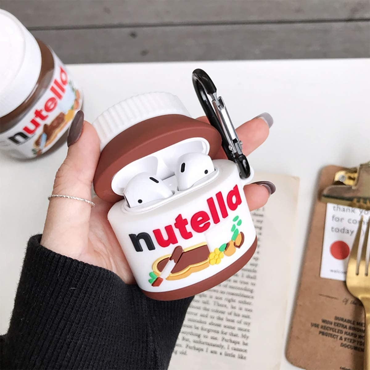 Model holding a silicone AirPods case modeled after a Nutella jar