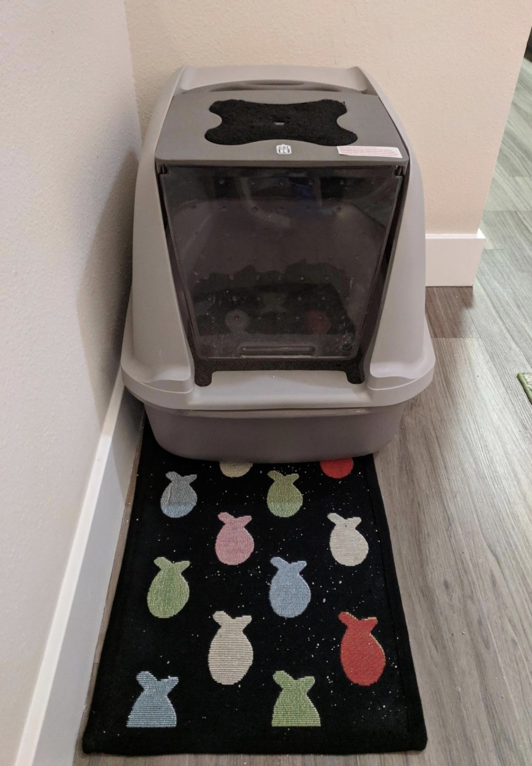 a grey catit litter box with a litter catching rug in front of it. This litter box has a window that cats can enter and exit from