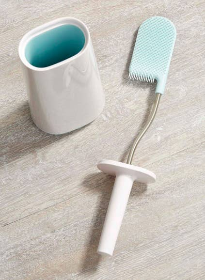 A flatlay of the toilet brush to show off its unusual flat, curved shape