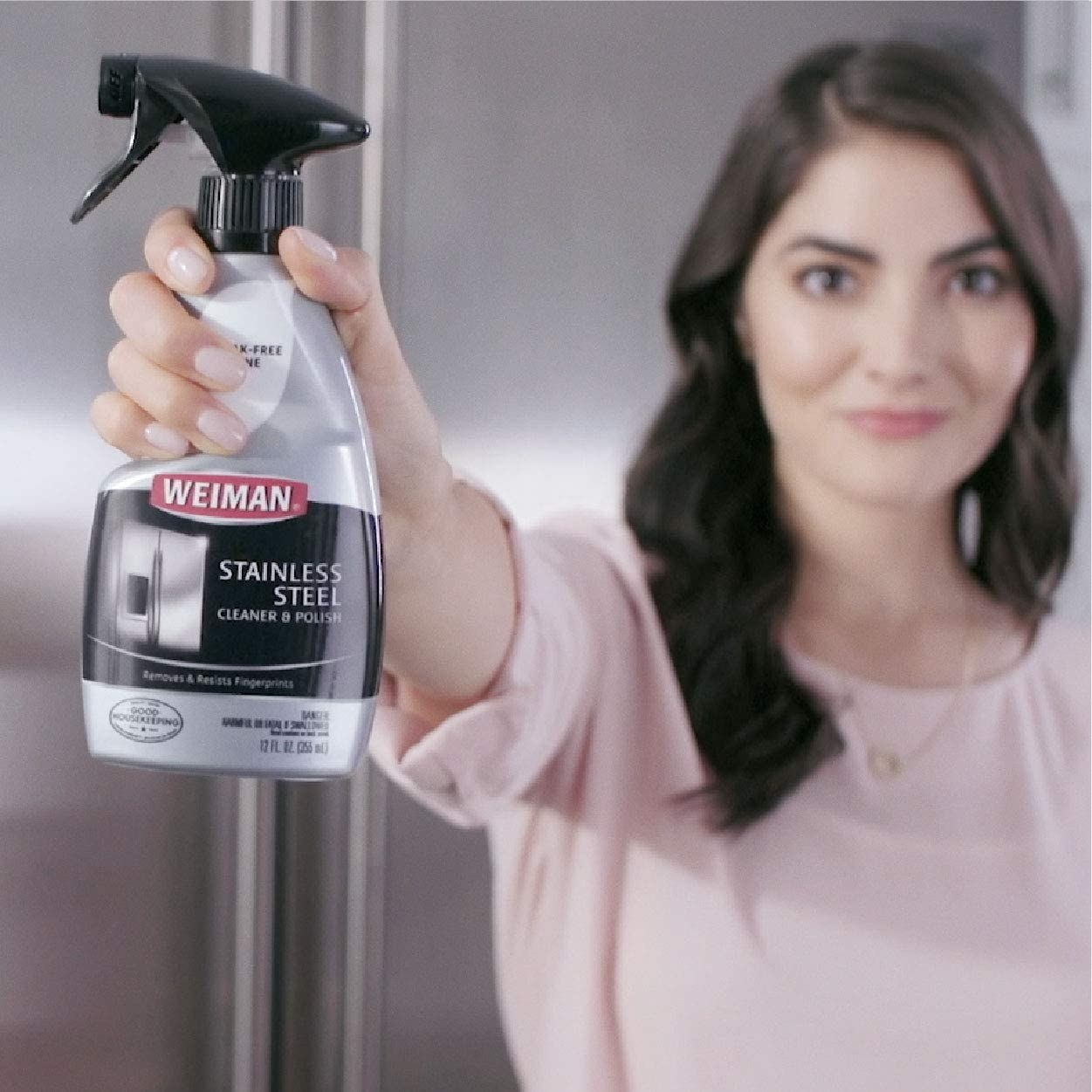 A person holds a bottle of the cleaning product in front of them