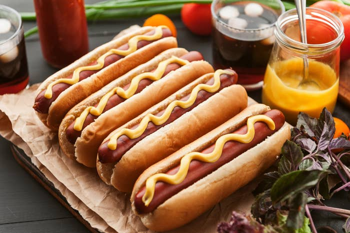 Four hot dogs in a line, each with an enticing line of mustard atop them