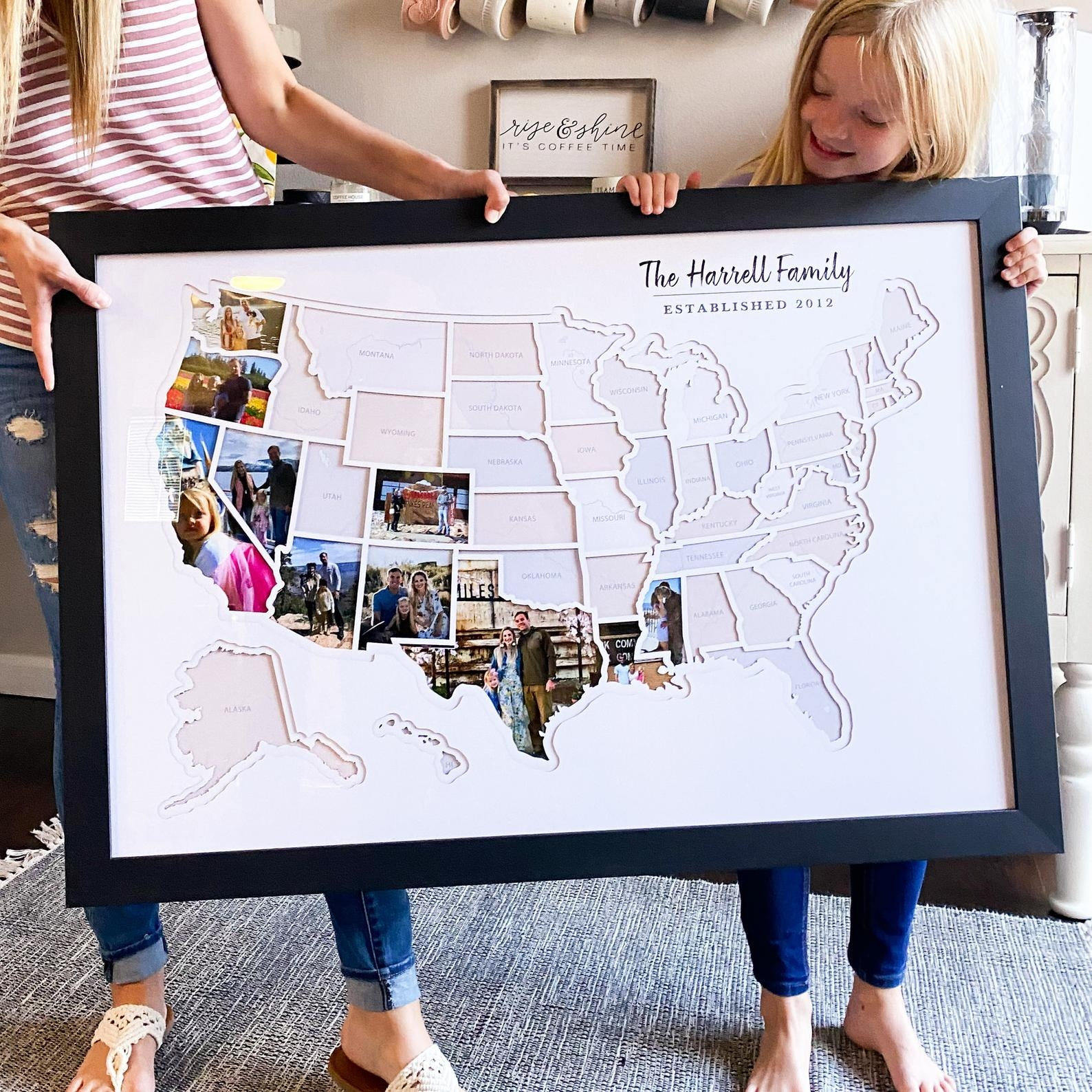 Two people holding a large frame of the U.S. map with some photos shaped to fit the states