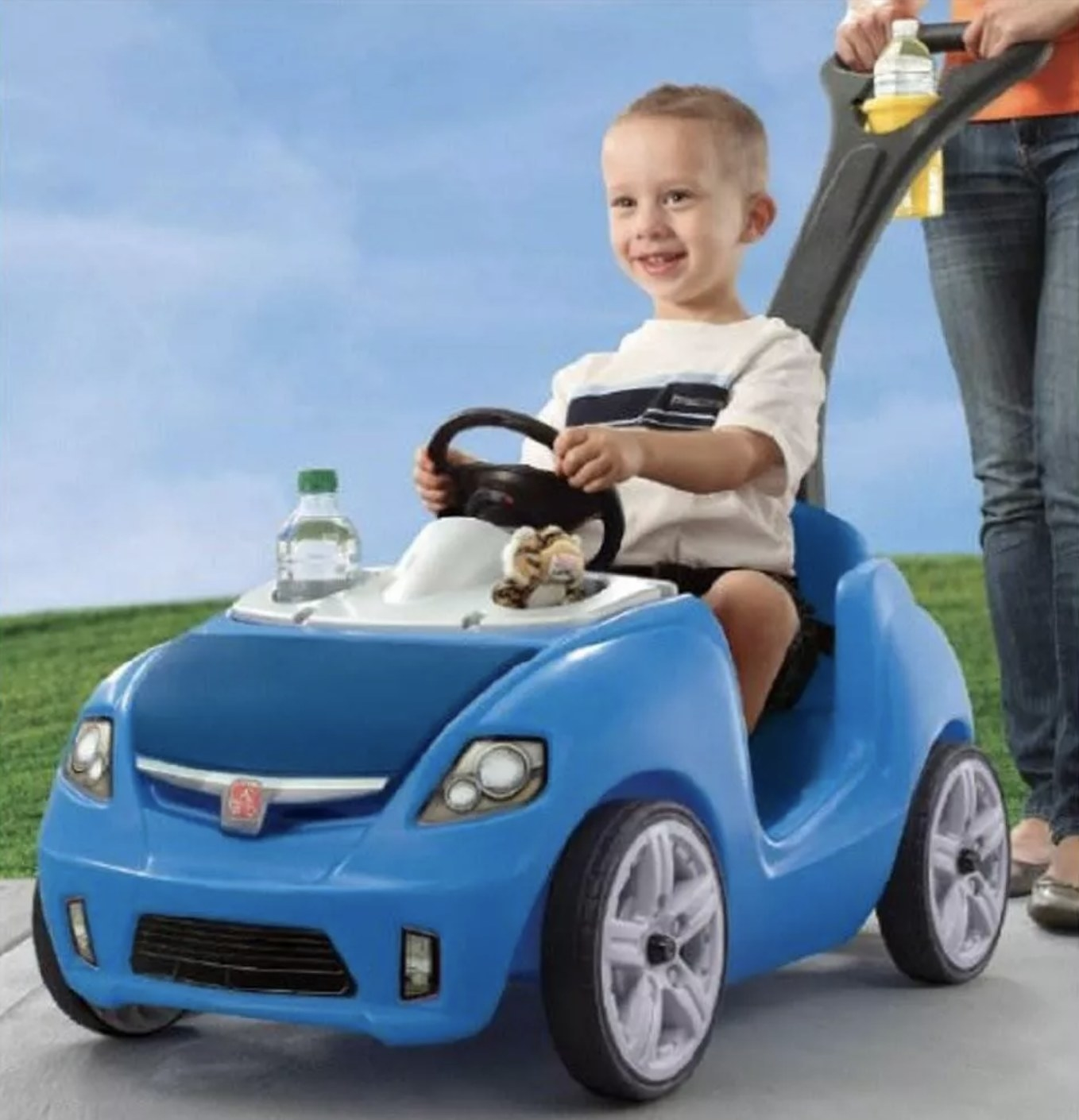 Person is pushing child in a blue push car