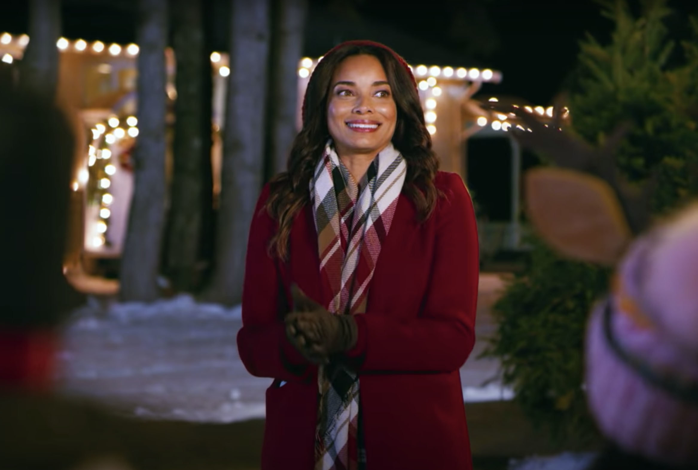 A woman dressed in festive attire smiles in a front yard