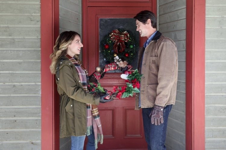 A woman hands a man a Christmas wreath in front of a red door