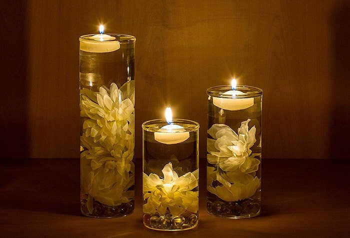 Three vases with flowers inside and candles floating on the water.