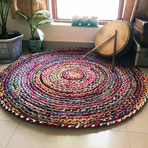 Rug spread out on the floor beside drums, plants, etc.