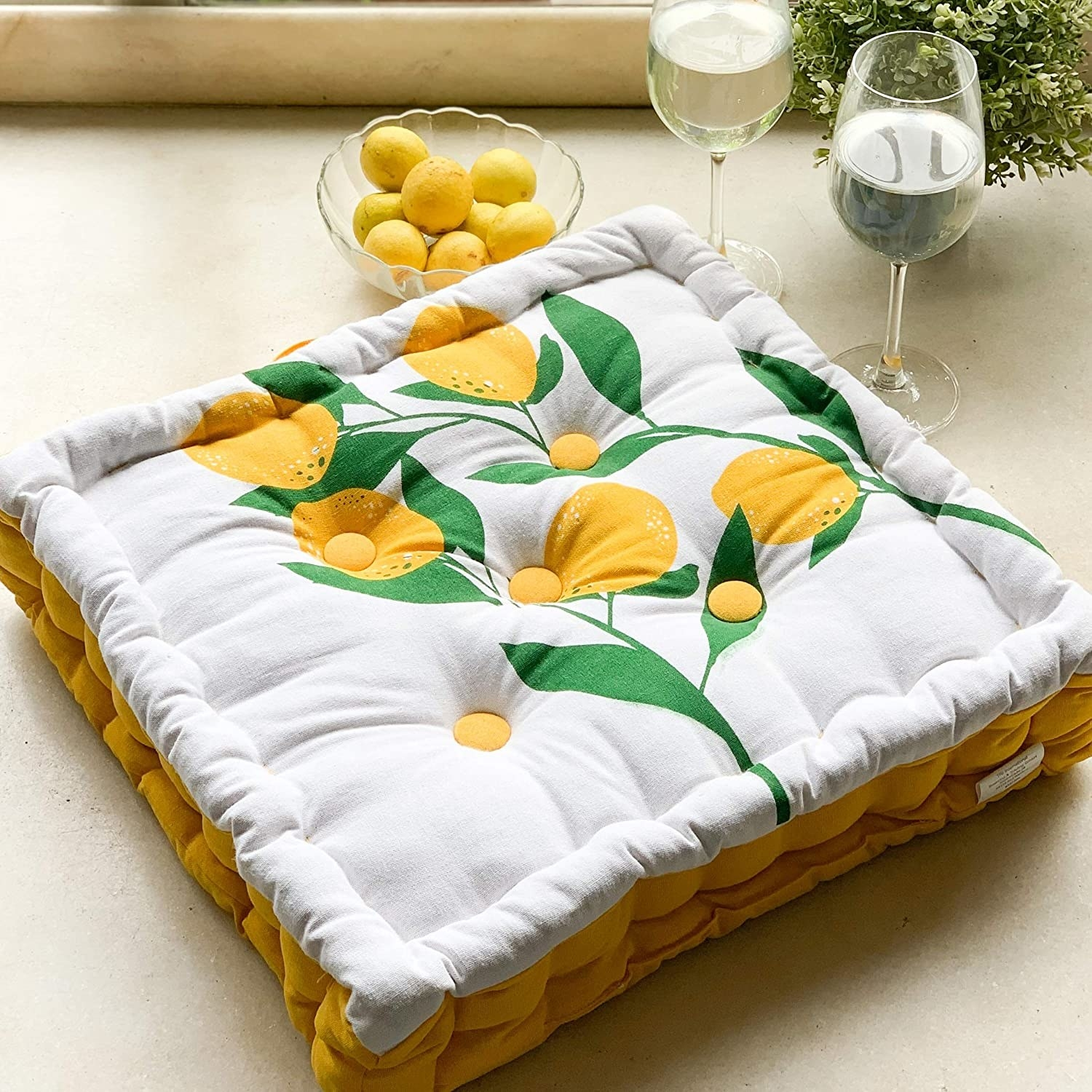 Floor cushion kept beside wine glasses filled with water and a bowl of lemons.
