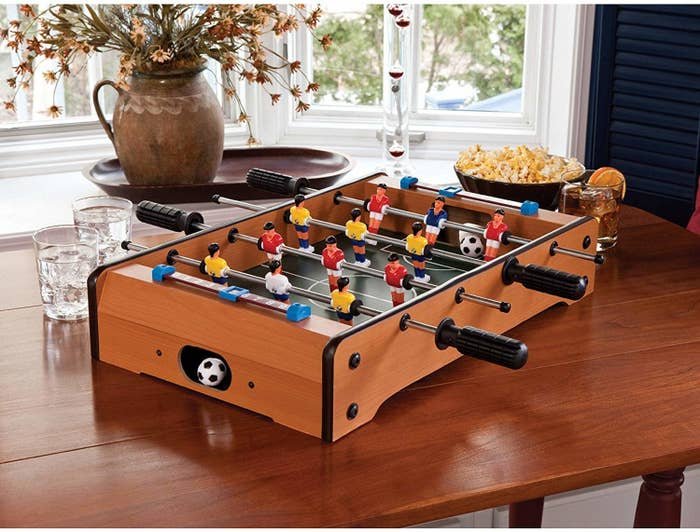 Foosball table kept on a dining table beside popcorn and drinks.