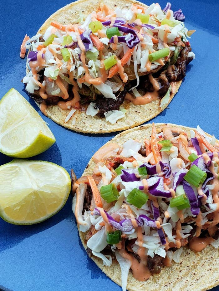 a close up of two Korean tacos on a plate, with bright green scallions, red cabbage, and a Sriracha mayo sauce on top