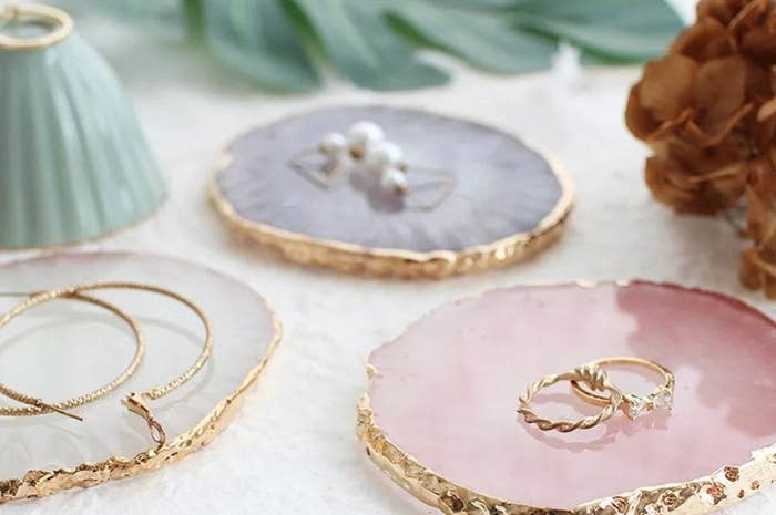 Three gold-dipped coasters with jewelry on them