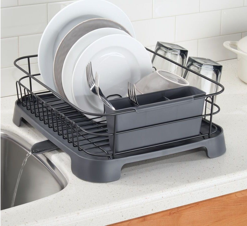 The drying rack in grey, with small legs that slightly elevate it off the counter and a small spout extending from the bottom to pour drained water back into the sink.