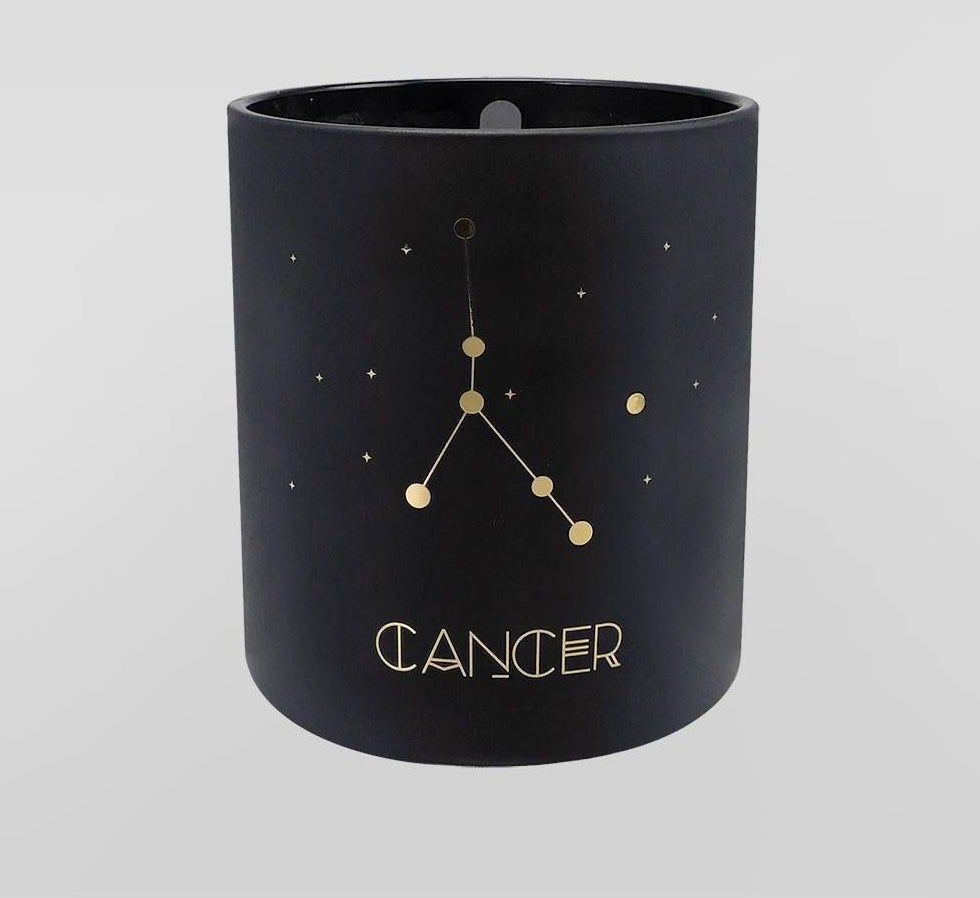 The candle in small black cylindrical jar, with the astrological sign and constellation written on the front in gold