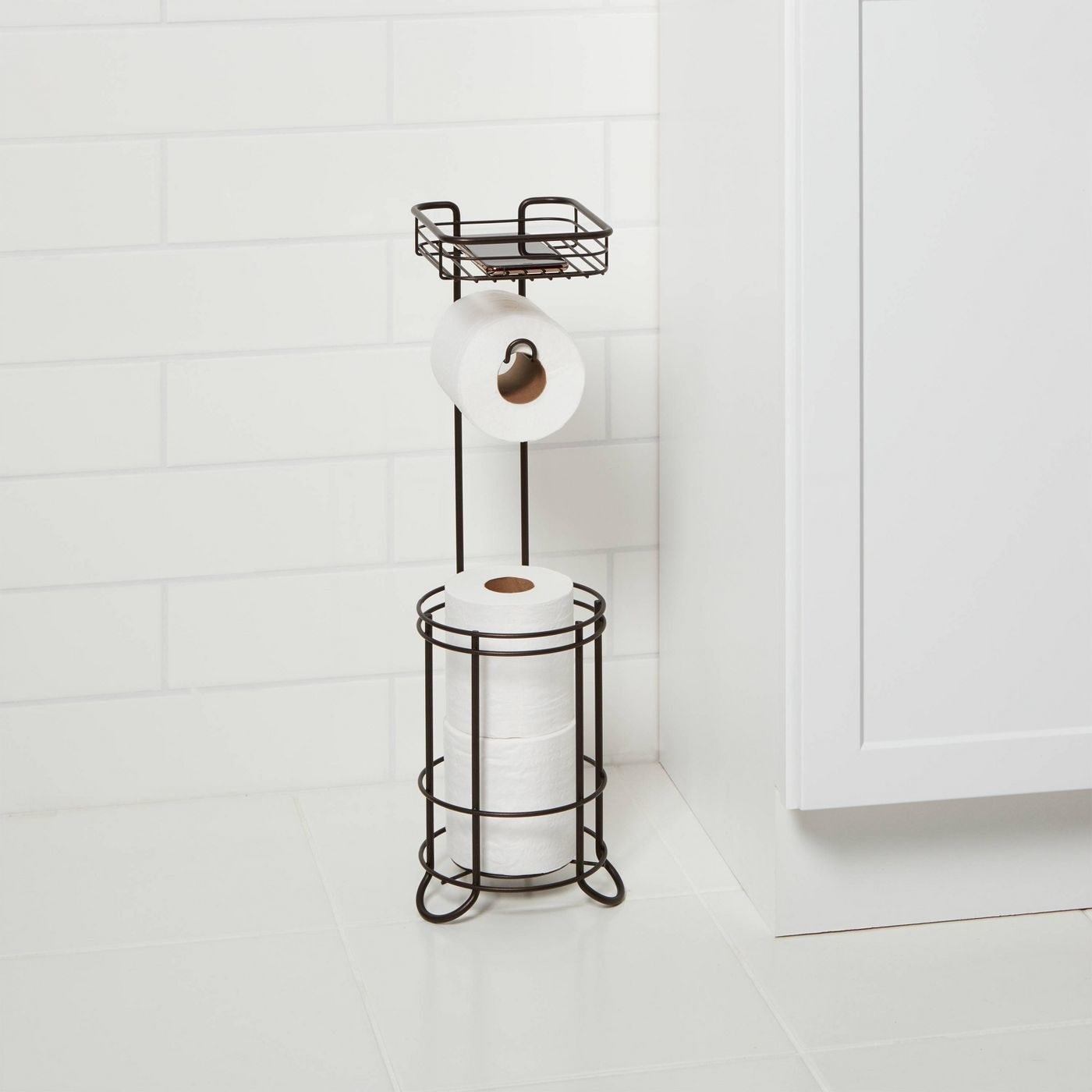 A black wire toilet paper caddy, with circular storage for two rolls at bottom, space to hang one roll in the middle, and a phone shelf at the top