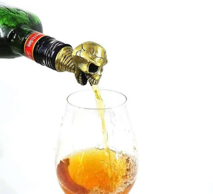 A skull decants alcohol into a glass