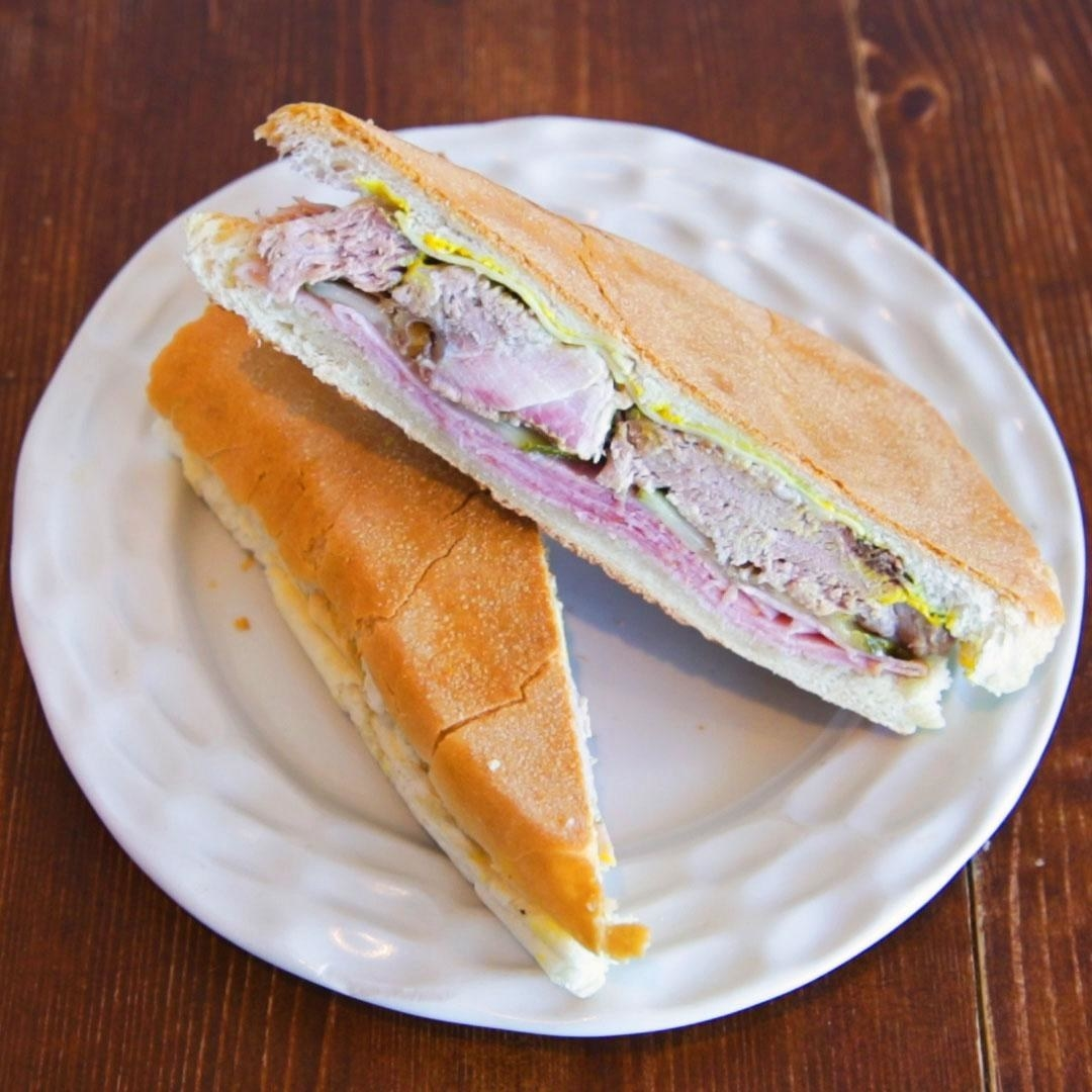 A Cuban sandwich sliced and plated.